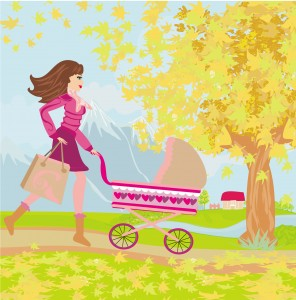 Young mom taking her baby for a stroll through park in autumn